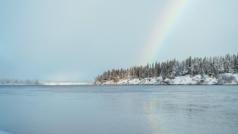 Rainbow on horizon reflected in water