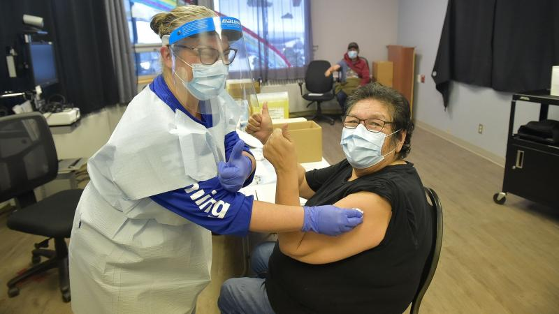 Woman gives thumbs-up while getting vaccinated
