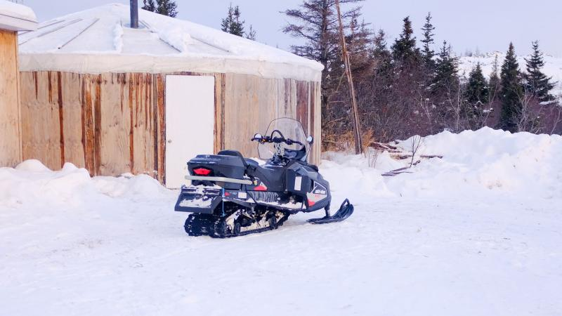 Snowmobile in front of wooden structure