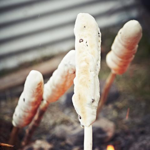Bannock on a stick cooking over fire