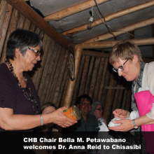 Bella M. Petawabano offers Dr Anna Reid a gift to welcome her to Chisasibi